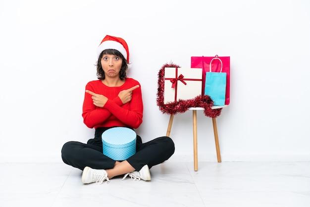 Молодой художник кавказской женщина держит палитру, изолированную на синем фоне, думая об идее, указывая пальцем вверх