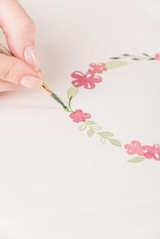 水彩絵の具とブラシで職場で紙の上に花のパターンを描く若いアーティスト