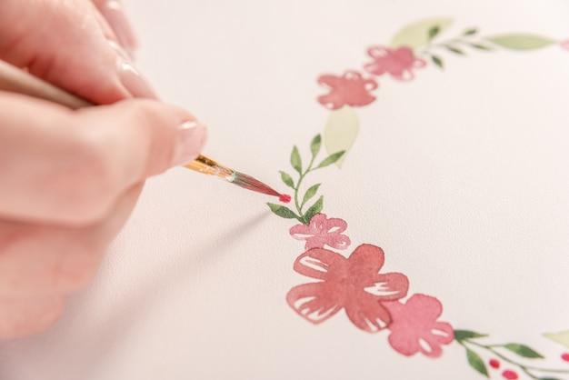 Молодой художник рисует цветочный узор акварельной краской и кистью на бумаге на рабочем месте
