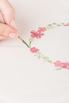 Young artist drawing flowers pattern with watercolor paint and brush on paper at workplace
