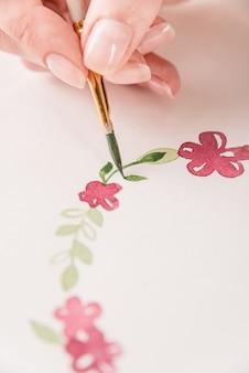 Giovane modello di fiori del disegno dell'artista con la pittura e la spazzola dell'acquerello su carta nel luogo di lavoro
