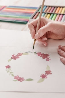 Giovane modello di fiori del disegno dell'artista con la pittura e la spazzola dell'acquerello nel luogo di lavoro