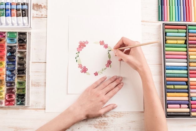 Young artist drawing flowers pattern with watercolor paint and brush at workplace