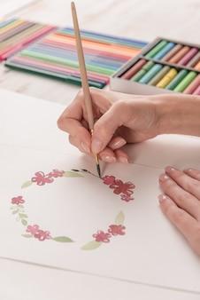 若いアーティストの水彩絵の具とブラシでパターンを描画