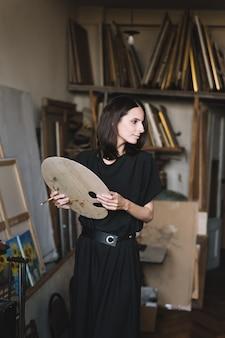 Юная художница девушка за работой в мастерской рисует полотно вдохновения