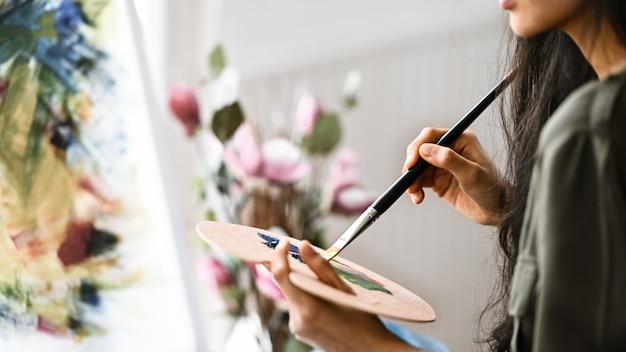 油絵の具を描きながらキャンバスを描く若いアーティストの女の子。