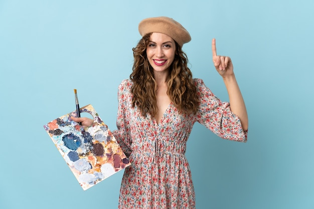 Девушка молодого художника держит палитру, изолированную на синем фоне, указывая вверх отличную идею