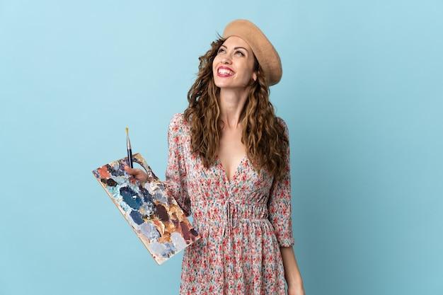 Девушка молодого художника держит палитру, изолированную на синем фоне, думая об идее, глядя вверх
