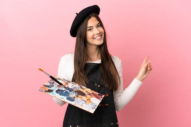 Девушка молодого художника держит палитру на изолированном розовом фоне, указывая назад
