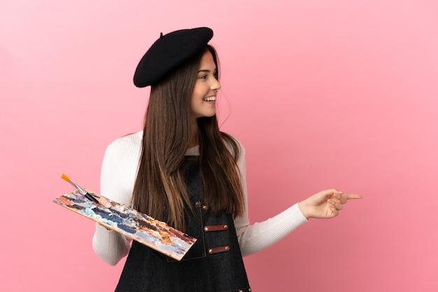 Молодая художница держит палитру на изолированном розовом фоне, указывая пальцем в сторону и представляет продукт