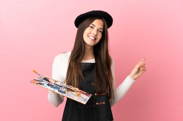 Девушка молодого художника держит палитру на изолированном розовом фоне, указывая пальцем в сторону
