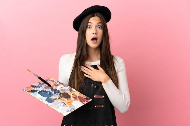 격리 된 분홍색 배경 위에 팔레트를 들고 젊은 예술가 소녀 놀라게 하 고 바로 보면서 충격