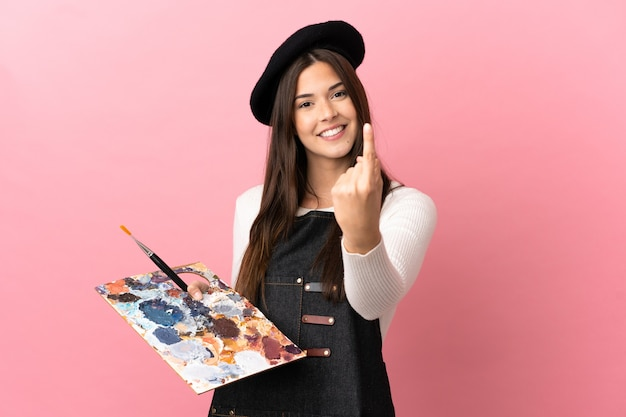 Young artist girl holding a palette over isolated pink background doing coming gesture