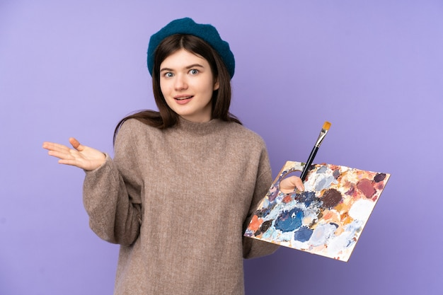 Young artist girl holding a palette over purple wall with shocked facial expression