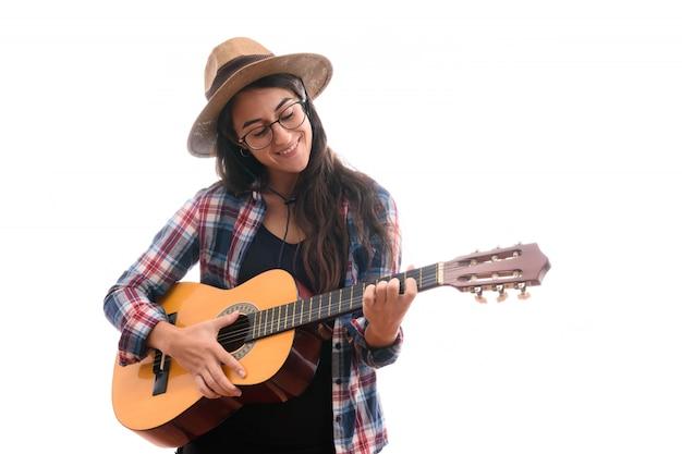 Молодая артистка играет на гитаре на белом фоне
