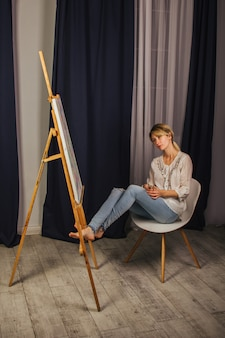 Young artist girl in a white shirt and blue jeans, paints a picture on canvas in the workshop. a young student uses brushes, canvases and easels. creative work for children and adults.