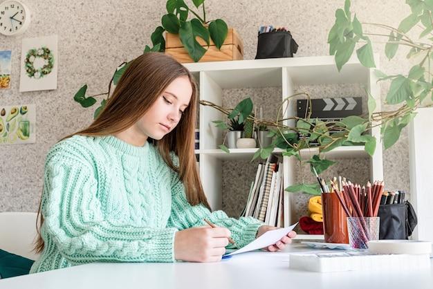 彼女のスタジオでブラシと紙を保持している若いアーティスト
