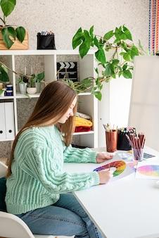 彼女のスタジオでカラーパレットを保持している若いアーティスト