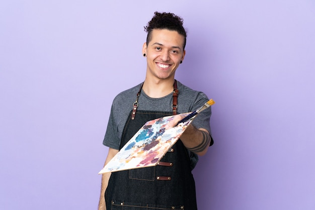 Young artist man holding a palette over isolated purple background with happy expression