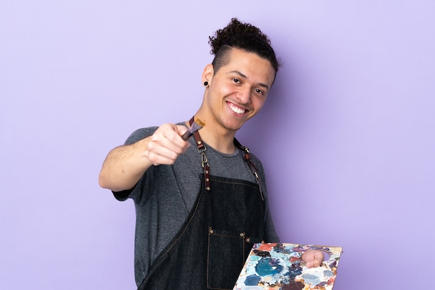 Young artist man holding a palette over isolated purple background