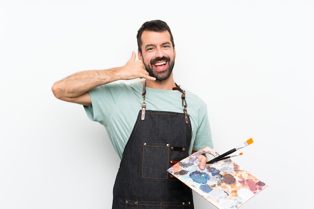 Young artist man holding a palette over isolated wall making phone gesture. call me back sign