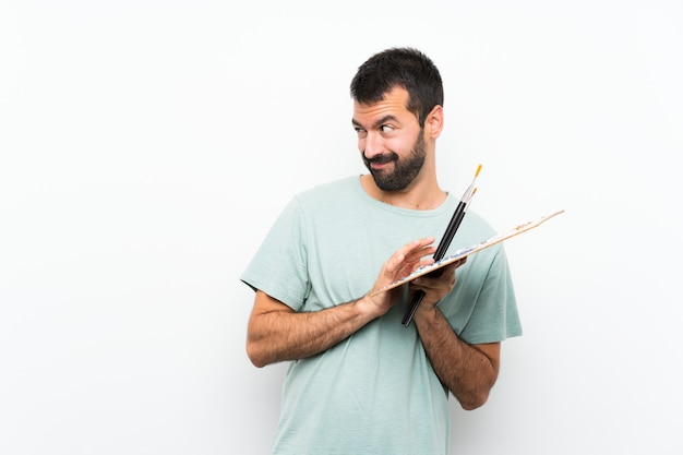 Young artist man holding a palette over isolated wall scheming something
