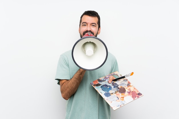 Young artist man holding a palette over isolated wall shouting through a megaphone