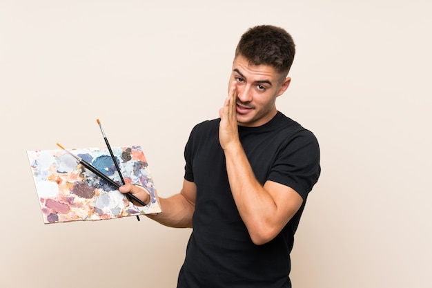 Young artist man over isolated wall whispering something