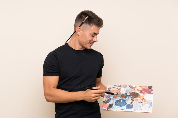 Young artist man over isolated wall