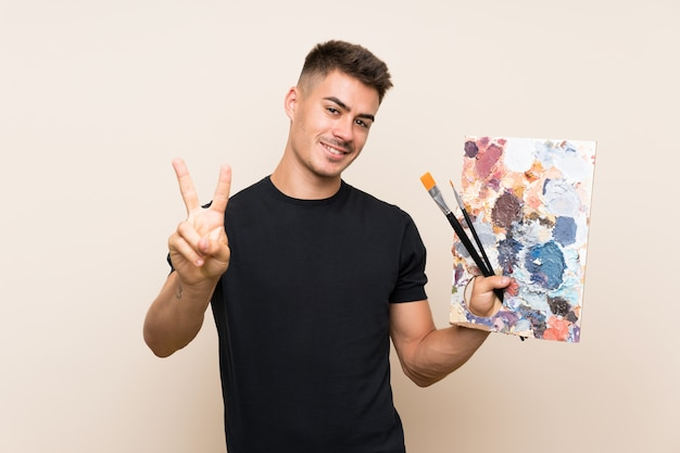 Young artist man smiling and showing victory sign