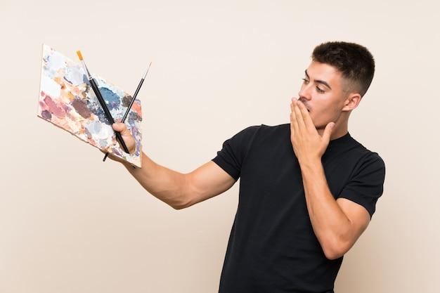 Young artist man with surprise and shocked facial expression