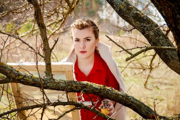 Молодой художник рисует пейзаж. женщина в красном платье стоит возле сухого дерева рисует, вид сверху