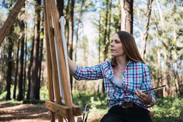 Молодой художник рисует в парке осенью.