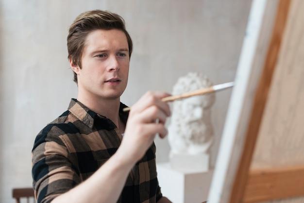 Молодой художник рисует на холсте