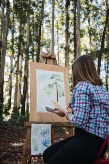 Юный художник пишет пейзаж на пленэре.