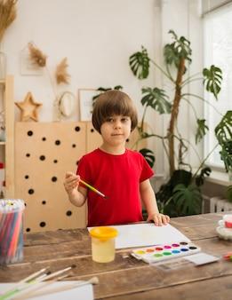 젊은 예술가는 흰 종이에 페인트하고 방의 앞을 봅니다.