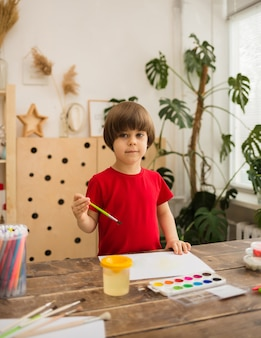 Young artist paints on white paper and looks at the front in the room