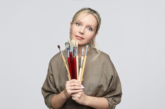 Young artist poses in front of the camera, pressing her brushes to her chin