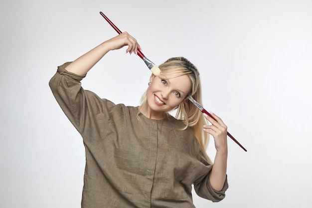 Young artist poses in front of the camera, pressing her brushes to her temples