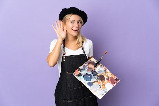 耳に手を置くことによって何かを聞いて紫色の背景に分離されたパレットを保持している若い芸術家ロシアの女性