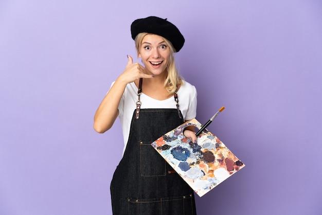 Молодой художник русская женщина, держащая палитру, изолированную на фиолетовом фоне, делая телефонный жест. перезвони мне знак