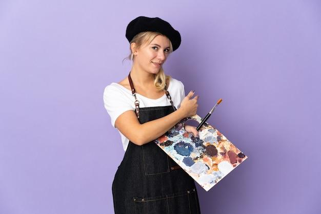 Молодой художник русская женщина, держащая палитру, изолированную на фиолетовом фоне, указывая назад