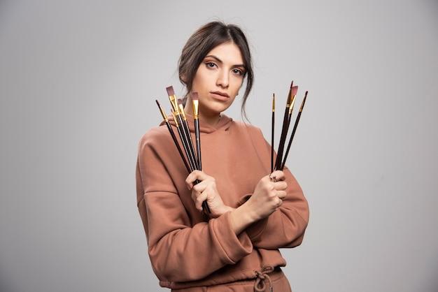 Giovane artista che mostra i suoi pennelli neri