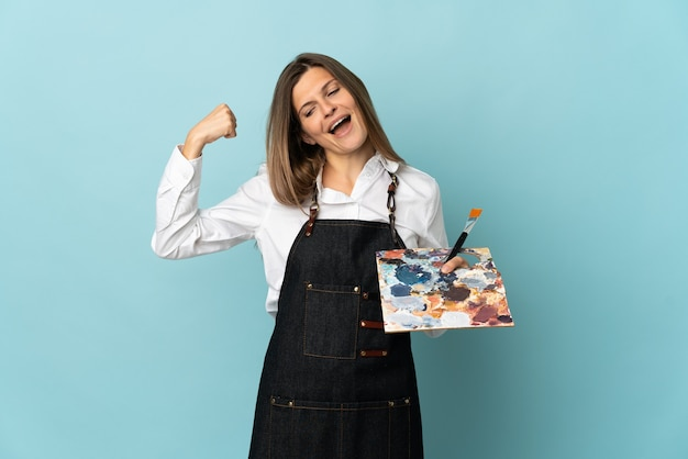 勝利を祝う青い背景に分離された若い芸術家スロバキアの女性