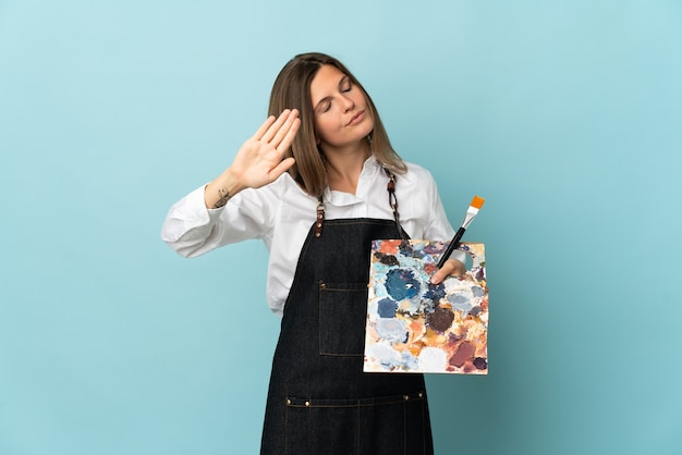 Молодой художник словацкая женщина изолирована на синем фоне, делая жест стоп и разочарована