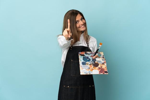 젊은 예술가 슬로바키아어 여자는 파란색 배경에 손가락을 보여주는에 고립