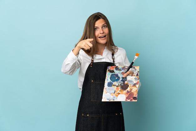 青い背景に分離された若い芸術家スロバキアの女性は驚いて正面を指しています