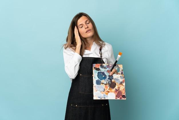 두통으로 파란색 배경에 고립 된 젊은 예술가 슬로바키아 여자