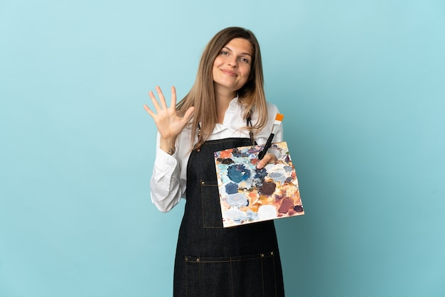 손가락으로 5 세 파란색 벽에 고립 된 젊은 예술가 슬로바키아어 여자