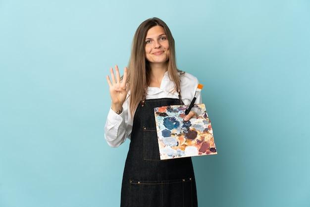 Молодой художник словацкая женщина изолирована на синей стене счастлива и считает четыре пальцами